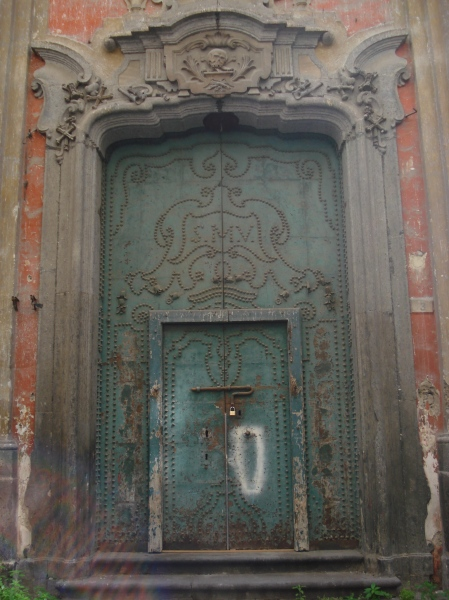 The wonderfully Baroque main door to an empty church in Naples